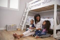 Storia della lettura della madre ai bambini nella loro camera da letto Fotografia Stock