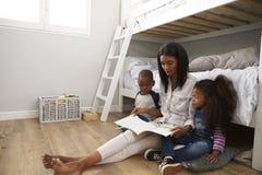 Storia della lettura della madre ai bambini nella loro camera da letto Fotografia Stock Libera da Diritti