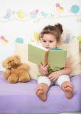 Storia della lettura della ragazza del bambino per l'orsacchiotto Immagini Stock