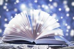 Storia di inverno Libro aperto su fondo blu nevoso di legno fotografia stock
