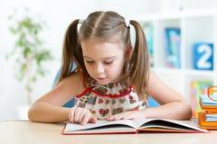 Storia sveglia della lettura della bambina dal grande libro dentro Fotografia Stock Libera da Diritti