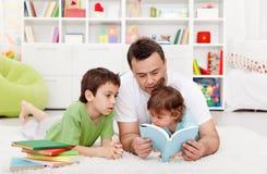 Storie della lettura del padre ai suoi ragazzi immagine stock libera da diritti