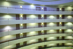 Stories in large hotel. Balconies and rows of indentical doors Stock Photo