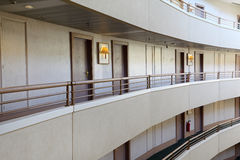Stories in large hotel. Grey balconies and rows of indentical doors Royalty Free Stock Images