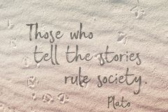 Stories on sand Plato. Those who tell the stories rule society - Plato quote on wavy sand surface royalty free stock image