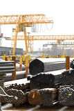 Storing of metal pipes in outdoor warehouse. With gantry cranes Stock Photography