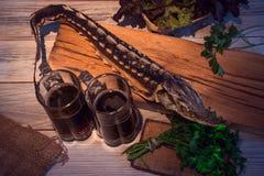 Storione secco con birra scura e verdi Fotografie Stock