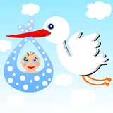 A stork carries a baby on a background blue sky Stock Photo
