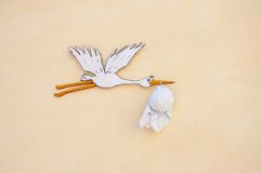 A stork carrying a baby wrapped in a bundle Royalty Free Stock Photos