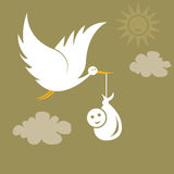 Stork carrying a cute baby. Child delivery by a white stork Royalty Free Stock Images