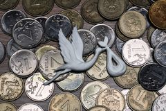 Stork som kommer med barn på bakgrunden av mynt, ryska pengar, metallmynt som spenderar på barn arkivfoto