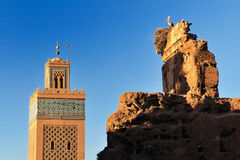 Stork watching the Minaret. A stork in its nest on ruins of an old wall in Marrakech while watching the Minaret of a Mosque Stock Photo