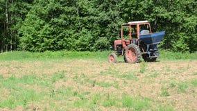 Storkfågel i åkerbrukt fält- och traktorsuggabovetefrö arkivfilmer