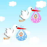 Storks carry babies on a background blue sky Royalty Free Stock Photo