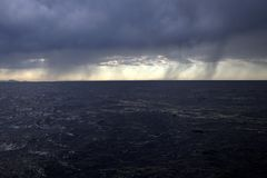 Storm. Clouds and rain in the ocean Stock Images