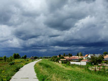Before the storm. Lanscape with road and willage with stormy clouds Stock Photos