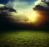 Storm. Dark clouds over field with grass Stock Images