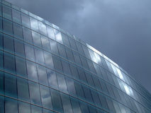 Before storm. Reflection of cloudy sky in glass wall building stock images