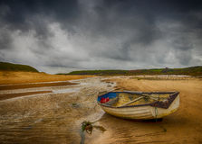 The Storm at Abeffraw, Anglesey, Wales. A small boat on the beach at Aberffraw, Anglesey, Wales. A storm is brewing in the background creating a very Stock Image