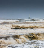 Storm at Aberdeen Lighthouse. Stormy seas churning up the beach at Aberdeen, Scotland, with the Nigg lighthouse in the background Stock Photo