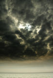 Storm approach. Over sea with sun hiding behind dark clouds stock images