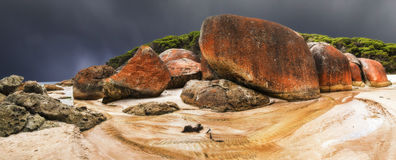 A storm approaches Squeaky beach. These giant boulders were an awesome sight before a black sky Stock Images