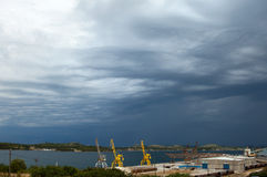 Storm approaching city harbour. Thick clouds above small harbour with cranes Royalty Free Stock Image
