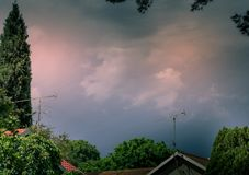 Storm clouds over residential houses royalty free stock images