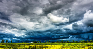 Storm Aproaching. Stormy blue and grey clouds over a green and yellow field Royalty Free Stock Photo