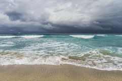 Storm in the Atlantic Ocean, waves, beach, coastline, white yacht on the horizon, low cloudiness. Varadero, Cuba royalty free stock image