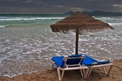 Storm on a beach. Beach couches and a lonely umbrella reached by a storm wave Stock Photos