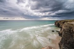 Storm on the beach of the Cathedrals. With threatening clouds on the horizon unloading rain Stock Images