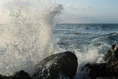 The storm begins at sea. the waves hit the rocks and the water is scattered. a sky covered with black clouds stock photography