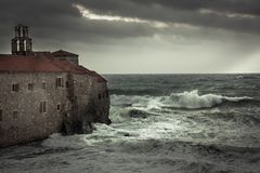 Storm with big stormy waves at  coastline crashing on the walls of a medieval castle on sea shore and dark dramatic sky in fall se Stock Images