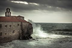 Storm with big stormy waves at  coastline crashing on the walls of a medieval castle on sea shore and dark dramatic sky in fall se Stock Photography