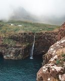 A storm blows the Mulafossur Waterfall. Sideways in the Faroe Islands Royalty Free Stock Images
