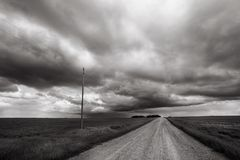 Storm blows through rural Alberta countryside. Black and white image of prairie storm with gravel road leading to horizon stock images