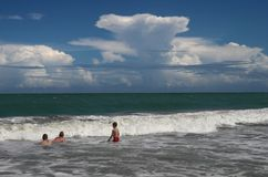 Storm brewing. Storm building over horizon on beach with swimmers royalty free stock image