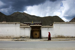 A storm is brewing. , a Lama walked past the house peacefully at Labrang Monastery Xiahe China Stock Photography