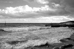 Storm brewing. Very moody sky due to storm brewing off shore at Sidmouth beach in Devon UK, shot in monochrome stock photos