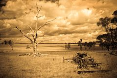 Storm brewing - old farm photo. Landscape of aged, sepia style image of a desolate farm with dead tree and old machinery and a storm brewing Royalty Free Stock Photography
