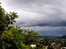 Storm Brewing Over Township. Storm clouds gathering over township in the valley from a lookout vantage point Royalty Free Stock Images