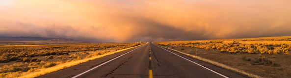 Storm Brews over Two Lane Highway At Sunset royalty free stock image
