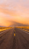Storm Brews over Two Lane Highway At Sunset stock photo