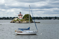 Storm Clearing as Lighthouse is Guiding Mariners. As the sun shines through overcast clouds, Pomham Rocks lighthouse will guide sailing vessels into Narragansett Royalty Free Stock Photography