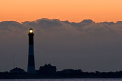 Storm Cloads and the Lighthouse at Sunrise. Fire Island Lighthouse at sunrise with an approaching storm coming Royalty Free Stock Photography