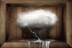 Storm cloud. A big rain filled cloud in a box with lightening and rain drops falling into a pool of water. Concept of trying to control the weather stock photos