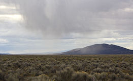 Storm Cloud Dropping Snow in Desert Royalty Free Stock Images