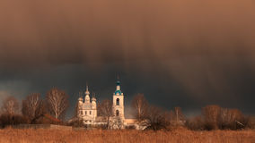 Storm cloud over the old church. In the spring of the old Orthodox Church of the Holy Trinity in the village Tolgobol, which was built in 1755, hung low Royalty Free Stock Photos