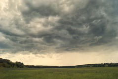 Storm cloud over yellow green fields forests and hills Stock Photos